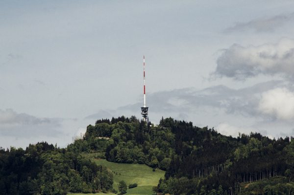 photo of a cell tower erected on a hillside with clouds on the background