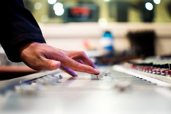 A hand slides the control on a soundboard google musics vs spotify