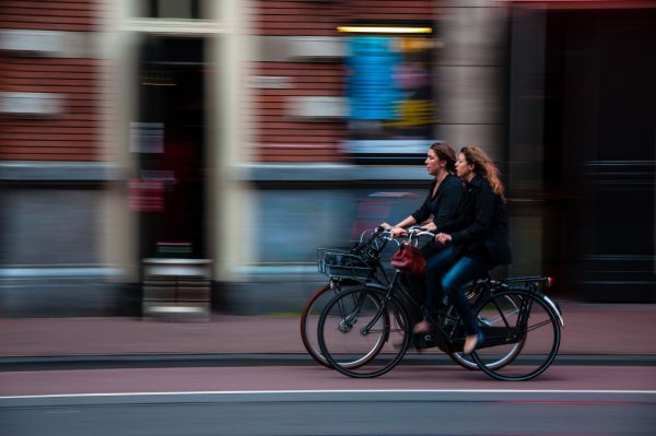 two women riding bicycles on blurred background