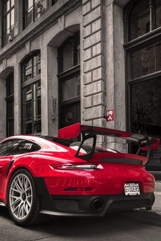 Cool and sleek, red Porsche car parked outside a building.