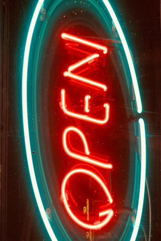 """Cool and awesome, vertical retro """"open"""" signage outside a bar in red and blue neon."""