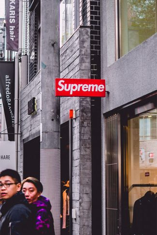 Bright red Supreme shop signage in a monotonous brick background.