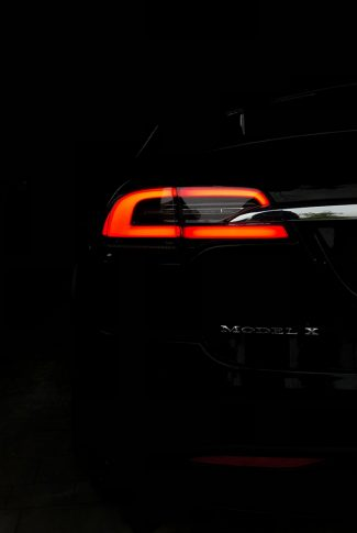 Black and sleek Tesla car's red light in the middle of a dark garage.