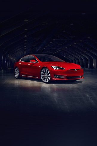 Smooth and classic red Tesla car parked on a wide garage.
