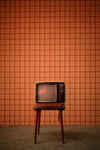 Old and vintage small television in a living room.