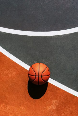 Nice and clear, flat angle shot of an orange basketball on court.