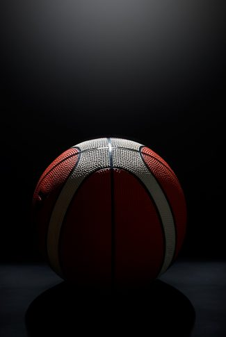 Cool and dark shot of a round basketball in black background.
