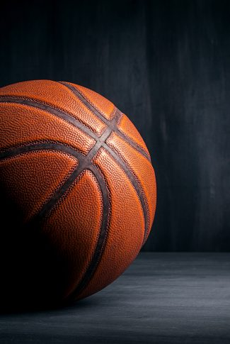 Nice and clear, angled shot of a basketball in gray background.