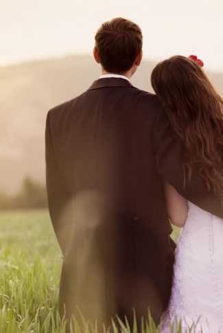 Nice and simple, lovely wedding couple sitting on grass.