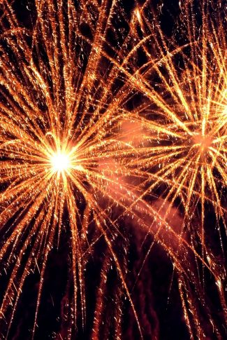 A warm color of a sparkling fireworks in the night sky at new year's eve.