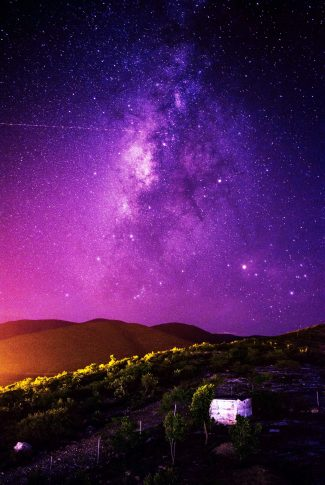 A color of a purple milky way shot by a photographer with a lots of stars in a field.
