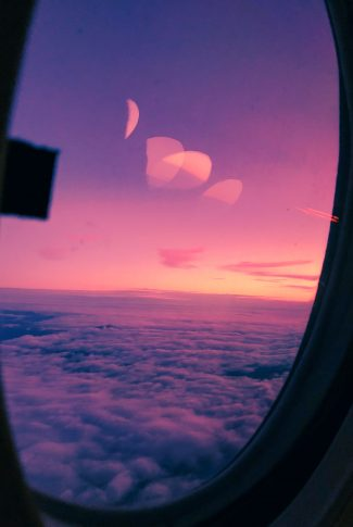A sunset on earth with a view of the clouds inside a window of a plane.