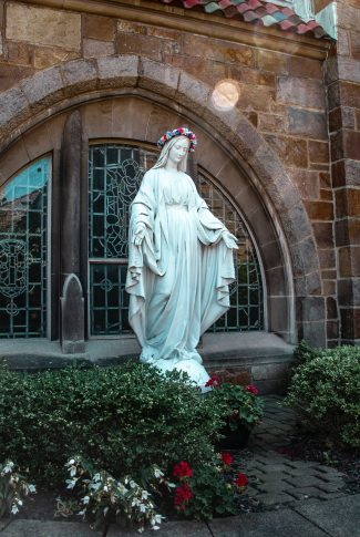 Nice and simple, solid white statue of Mary in the garden with flowers.