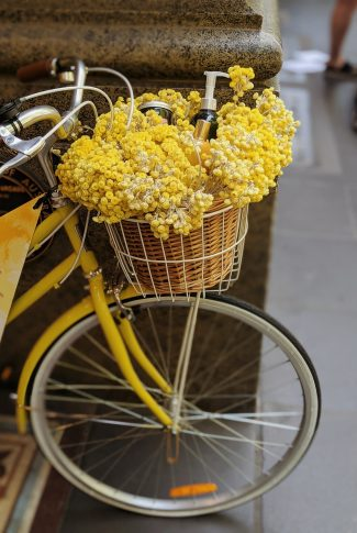 This adorable bike has a basket filled with yellow flowers.