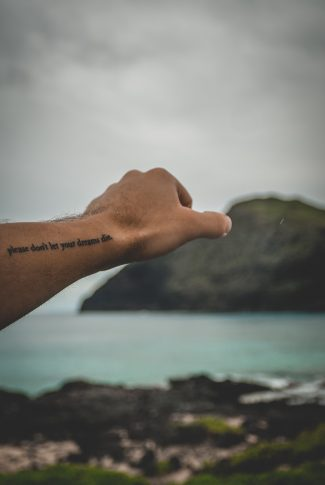 Dreams are what drives people to be the best they can be. Keep on dreaming! A motivational quote wallpaper written on a man's arm with a beach scenery in the background.