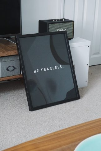 Turn your fears into cheers. Rather than it to hold you back, let it be your drive to persevere. A motivational quote wallpaper on a black photo frame.