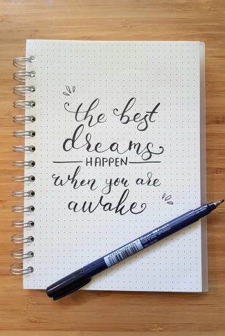 There is no better feeling in the world than to know that your dreams came into realization. A motivational quote wallpaper written on a notebook in calligraphy.