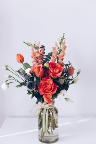 A beautiful wallpaper of a flower bouquet in shades of orange in a clear jar vase.