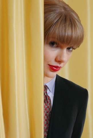 A wallpaper of Taylor Swift in a suit and hiding behind yellow curtains.