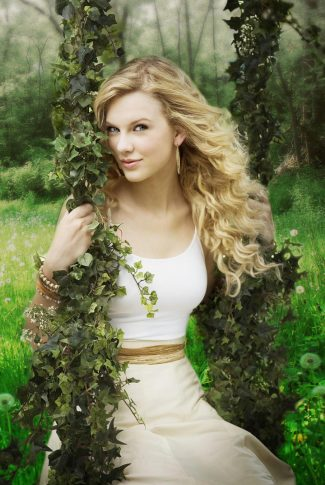 A beautiful wallpaper of Taylor Swift on a plant-filled swing outdoors.