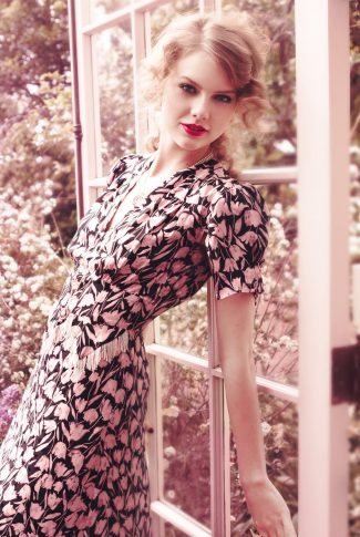 A beautiful wallpaper of Taylor Swift in a flower-patterned dress and leaning against a door.