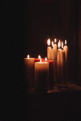 A classic wallpaper of lighted candles on a black background.