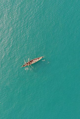 A beautiful summer wallpaper of people rowing a boat through the ocean.