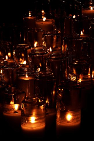 A beautiful wallpaper of lighted candles in jars.