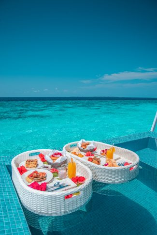An aesthetic summer wallpaper of meals in a floating tray by the pool with a beautiful view of the ocean.