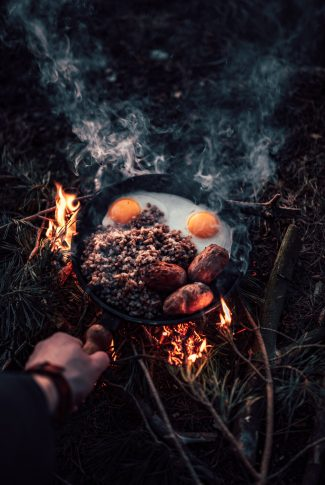 A cool wallpaper of a person cooking breakfast on a bonfire.
