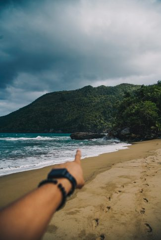 A cool summer wallpaper of a person pointing to the beach with mountains.