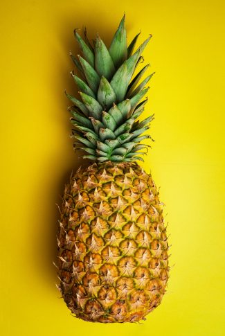 A cool summer wallpaper of a pineapple on a yellow background.
