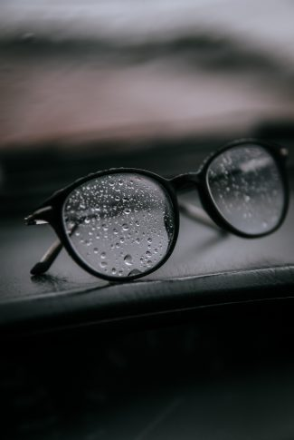 A cool wallpaper of raindrops on a pair of eyeglasses.