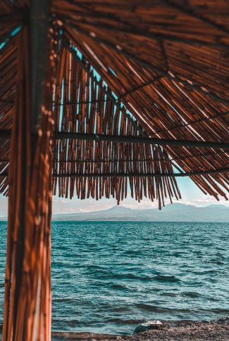 A cool summer wallpaper of a wooden umbrella shed by the beach.
