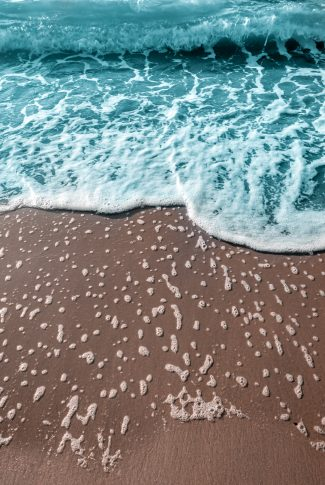 An aesthetic summer wallpaper of the beach sand and sea water.