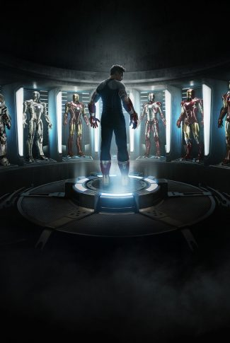 A movie wallpaper of Tony Stark in the middle of the room surrounded by his Iron Man suits from Iron Man 3.