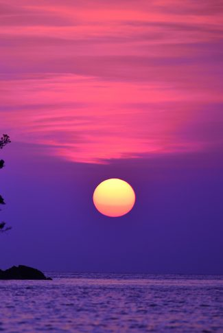 A scenic wallpaper of a sunset at the ocean with the sky in pink and purple.