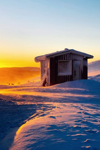 A scenic winter wallpaper of a tiny shed covered in snow.