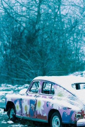 A cool winter wallpaper of a pink retro car covered in snow.