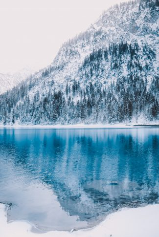 A scenic wallpaper of a deep blue lake at the snowy mountain in the middle of winter.