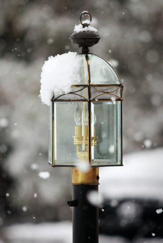 A scenic winter wallpaper of a lamppost in black and gold with the snow falling.