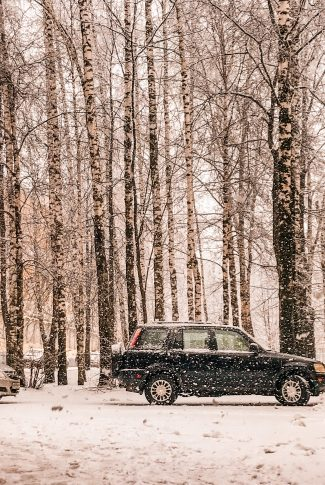 A cool winter wallpaper of cars parked at a forest with the snow falling.