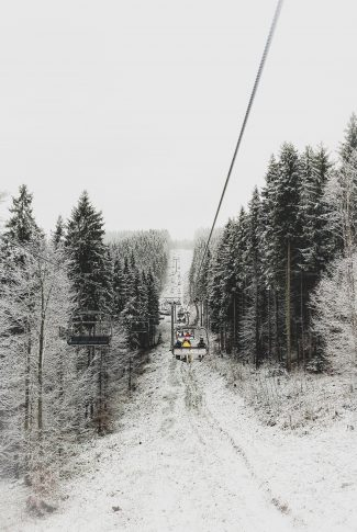 A beautiful winter wallpaper of people in cable cars surrounded by snowy forest trees.