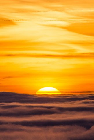 A beautiful wallpaper of a sunset from the huge bed of clouds.