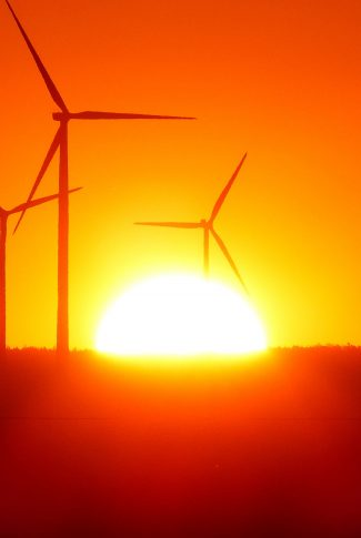 A mesmerizing wallpaper of a sunset by the wind turbines.